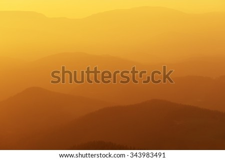 distant mountains at the sunset with warm colors - stock photo