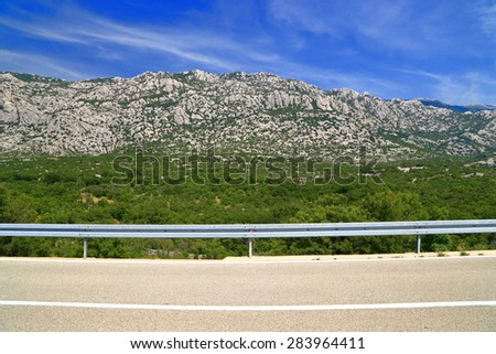 Distant mountains covered with green bushes along sunny road on Dalmatian coast, Croatia - stock photo