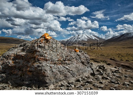 Distant mountains with rock outcropping and yellow flag - stock photo