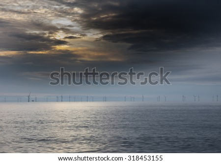 distant off shore wind turbine farm set against a background of storm clouds at sunrise  - stock photo