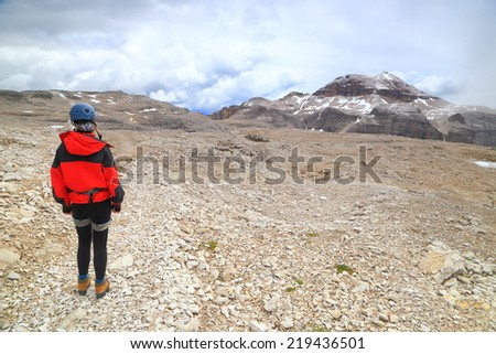 Distant Piz Boe summit and climber woman on the Meisules plateau, Sella massif, Dolomite Alps, Italy - stock photo