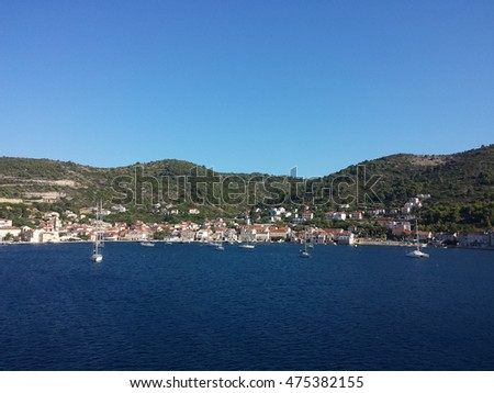 Distant sea city view with sailing boats