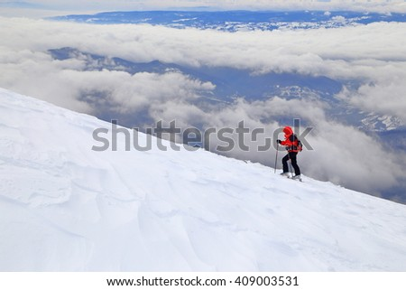 Distant skier climbs on touring skis in nasty weather - stock photo