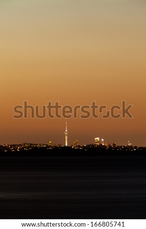 Distant skyline of Auckland City, New Zealand, with Sky Tower illuminated in twilight dusk after sunset - stock photo