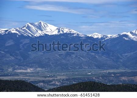 Distant tall snow capped mountain range in Colorado near Salida. - stock photo