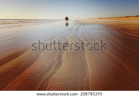 Distant unrecognisable couple walking on beach, with instagram filter. - stock photo