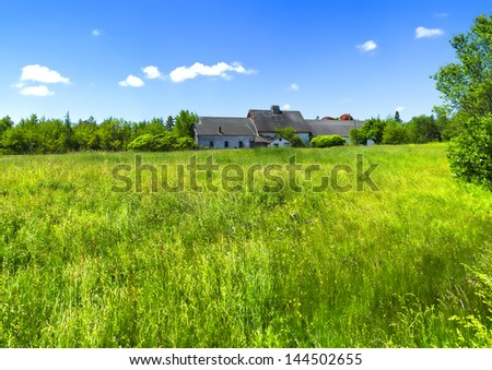 Distant view of a deserted farmhouse with lush green field in the foreground. - stock photo