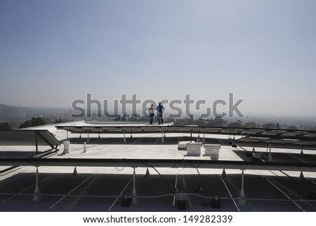 Distant view of maintenance workers near solar panels on rooftop in Los Angeles; California - stock photo