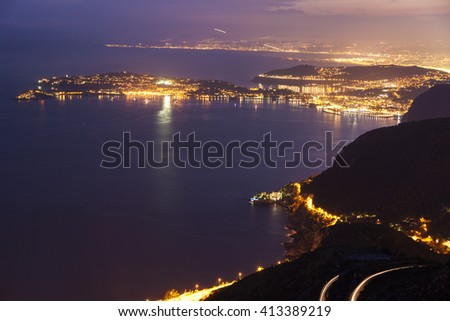 Distant view of Saint Jean Cap Ferrat and Nice at sunset seen from Monaco. Saint Jean Cap Ferrat, French Riviera, France. - stock photo