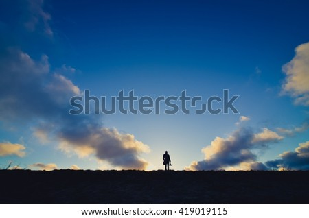 Distant View Of Silhouette Man On Field Against Sky At Sunset