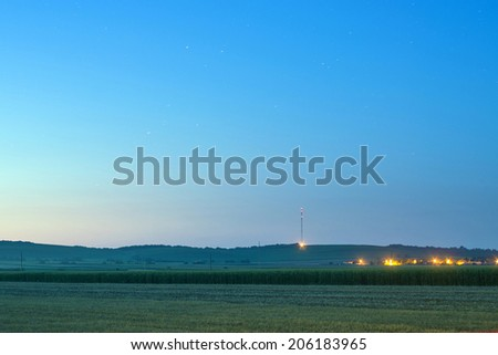 Distant vineyard hills and agricultural corn field with village lights at summer night - stock photo