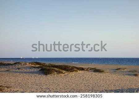 Distant white yachts and boats near sandy ocean shores of Mandalay Beach, Oxnard, California - stock photo
