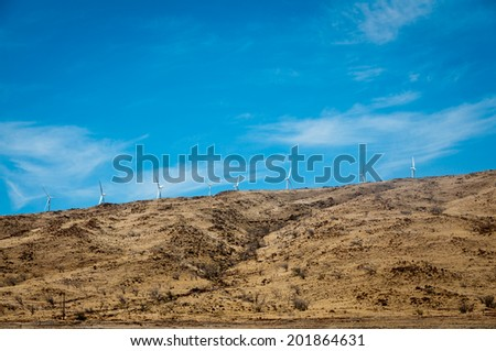 Distant wind turbines on a steppe hill on Maui - stock photo