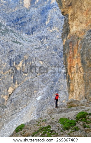 Distant woman hiking under huge rock walls on Durissini trail, Cadini di Misurina, Dolomite Alps, Italy - stock photo