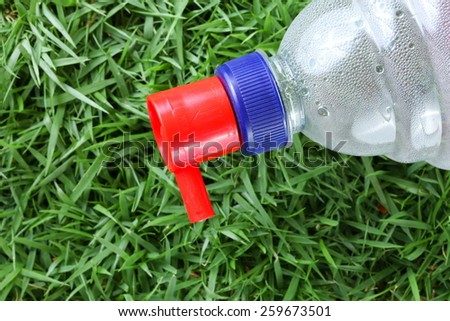 Distilled water for car battery bottle  in the scene show the head filling cap put on grass background represent the car battery necessary related concept idea. - stock photo