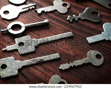 Distinctive keys. Many odd shaped keys on old wood table . Security and encryption, concept image.  - stock photo