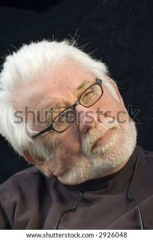 Distinguished mature man with white beard and mustache, eyeglasses, head tilted, looking thoughtfully upward, like a film director - stock photo