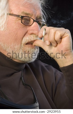 Distinguished mature man with white beard and mustache, eyeglasses, thumb to mouth, cigarette in hand, looking thoughtful, like a film director - stock photo