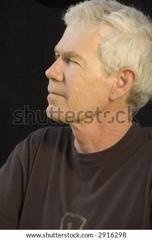 Distinguished mature white man in dark T-shirt, gray hair, dark background, side view - stock photo