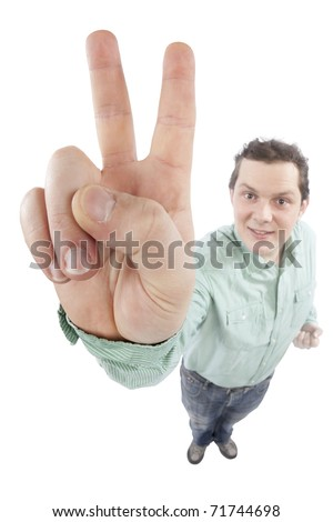 Distorted image of a young man gesturing victory or peace sign. Fish-eye lens used, focus is on the hand. Studio shot. Isolated on pure white background