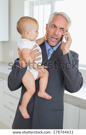 Distracted businessman holding his baby in the morning before work at home in the kitchen - stock photo