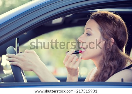 Distracted driver. Side view window view beautiful young woman applying makeup while driving car, isolated city traffic background.  - stock photo