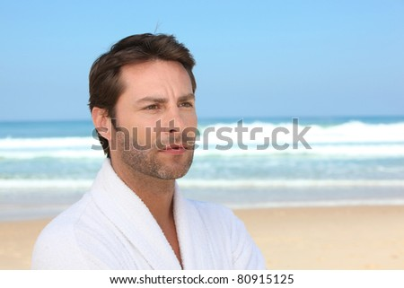 Distracted man standing on the beach in a bathrobe - stock photo