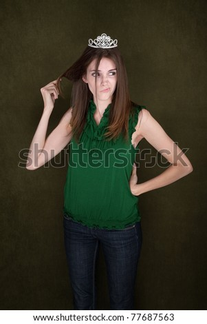Distracted young woman wearing a tiara twirls her hair - stock photo