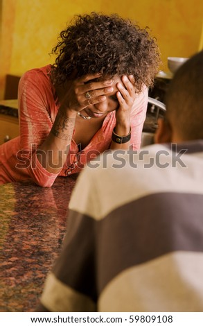 Distraught African-American woman and male talking in kitchen - stock photo