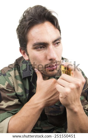 distraught military soldier veteran ptsd drinking a shot of liquor solated on white - stock photo