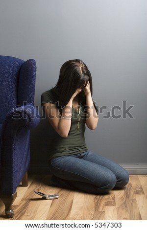 Distraught young woman crouched on floor, hands covering face. - stock photo