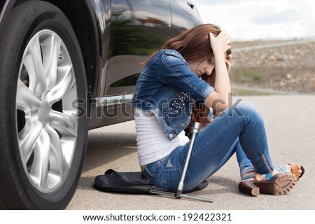 Distraught young woman waiting for roadside assistance sitting alongside her broken down car on a rural road with her head in her hands - stock photo