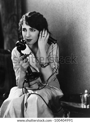 Distressed woman using telephone