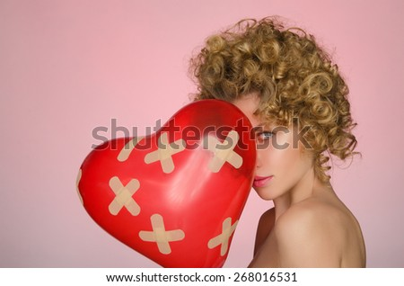 distressed woman with ball in shape of heart on pink background - stock photo