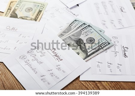 Distribution of money, financial planning, dollars in envelopes, on wooden table background - stock photo