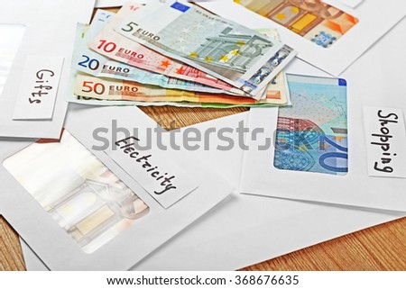 Distribution of money, financial planning, euro in envelopes, on wooden table background