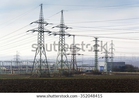Distribution power station with electricity pylons and dramatic cloudy sky background