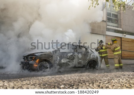 DISTRITO FEDERAL, MEXICO- JANUARY 22: Two firemen coordinate efforts between them as to be sure a still burning car is completely extinguished as seen in Mexico city on January 22, 2014. - stock photo