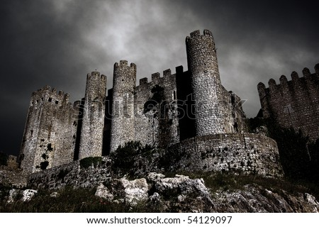 Disturbing scene with medieval castle at night with stormy sky - stock photo
