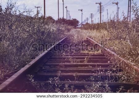 disused railway track on the field,warm light tone - stock photo