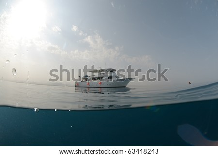 Dive boat on a calm ocean with mountain desert background - stock photo