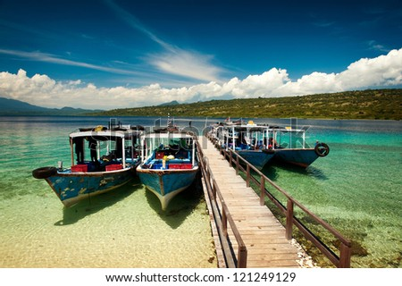 Dive boats wait at the dock on Menjangan Island, Bali, before taking SCUBA tourists out on the magnificent reefs in Bali Barat National Park. - stock photo