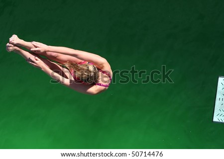 Diver above green water with end of diving board visible - stock photo