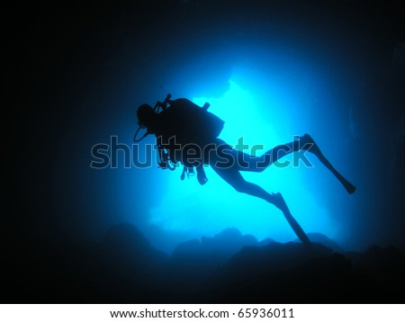 Diver at a cave facing bluewater in the background - stock photo