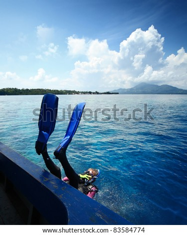 Diver doing back flip into blue transparent sea from a boat's board - stock photo