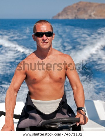 Diver driving speedboat to a dive site