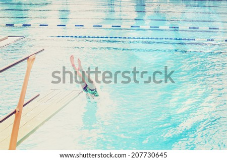 Diver entering the water (focus on the diving board) - stock photo
