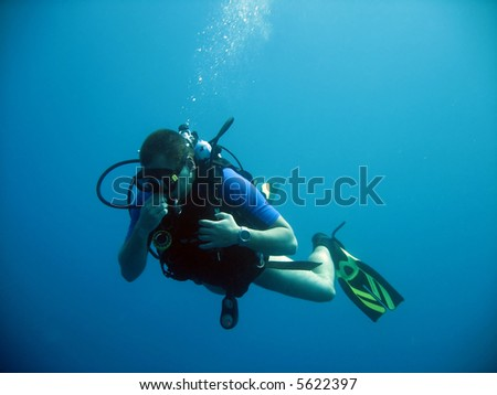 Diver, equalising pressure in his mask and ears - stock photo