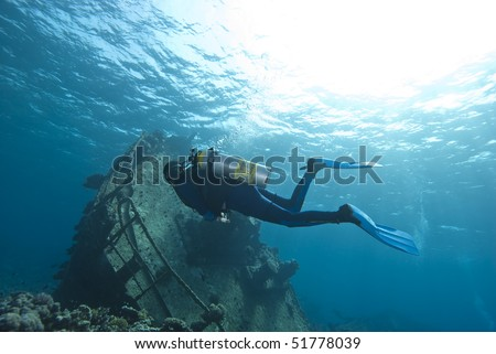Diver exploring the remains of the Kormoran shipwreck, surrounded by hard coral growth. Sharm el Sheikh, Red Sea, Egypt.