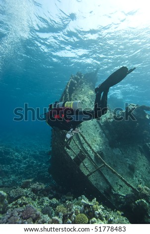 Diver exploring the remains of the Kormoran shipwreck, surrounded by hard coral growth. Sharm el Sheikh, Red Sea, Egypt. - stock photo